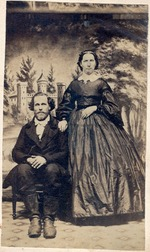 Peter Simpkins and Lucy Simpkins.  Black & white formal portrait.  Lucy Simpkins is standing with her hand on Peter's shoulder.